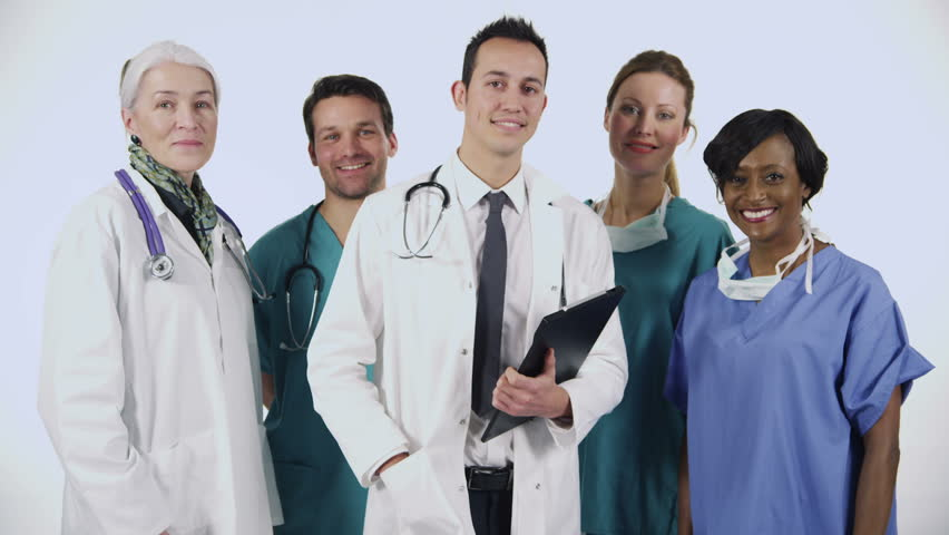 Portrait of a team of medical personnel of mixed ages and ethnicity isolated on white. They are talking amongst themselves then they all look to the camera and smile.