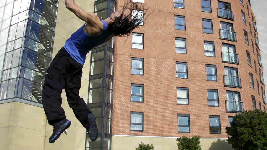 Tumble - a free runner back flips in an urban setting in super slow motion