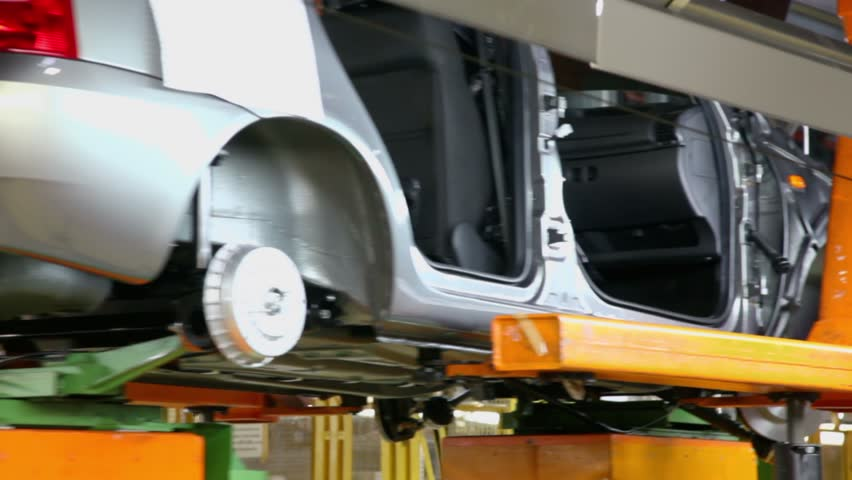 Conveyor transporter transfers unfinished car, closeup view at factory workshop