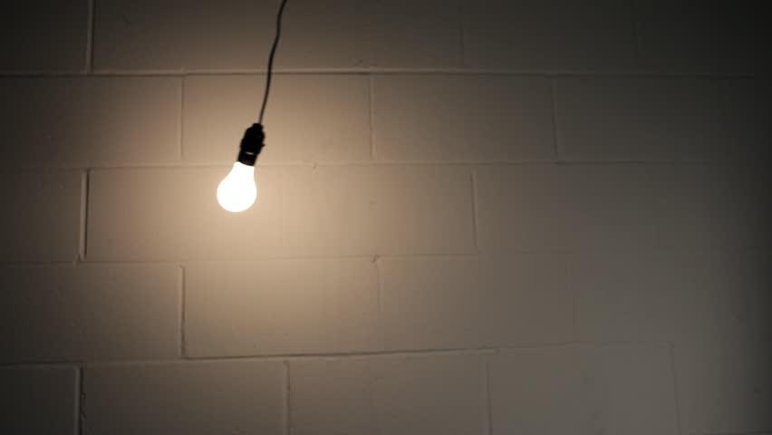 Abstract Swinging Light Bulb In Dark Room Stock Footage