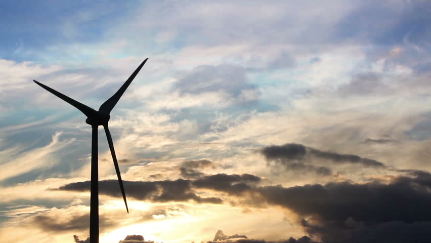 Rotating wind turbine at sunset, silhouetted against a colourful sky with moving clouds. Copy space to the right of frame. - HD stock footage clip