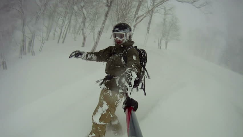 Extreme Snowboarder Blasts Through Backcountry Powder Snow. Snow flies