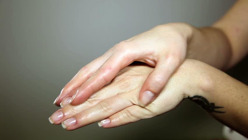 Close up shot of a woman`s hands spreading a cream over the fingers - HD stock video clip