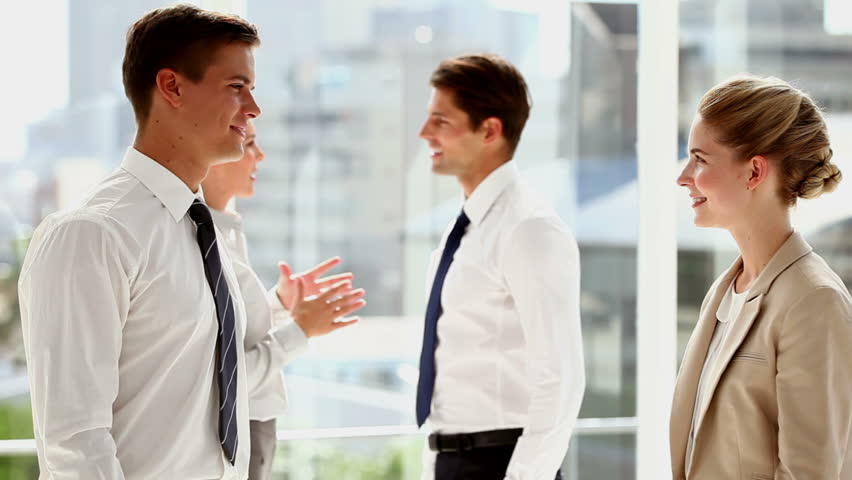 Business people shaking hands and walking away in busy modern office