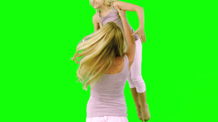 Mother lifting and spinning her daughter on green screen in slow motion - HD stock footage clip