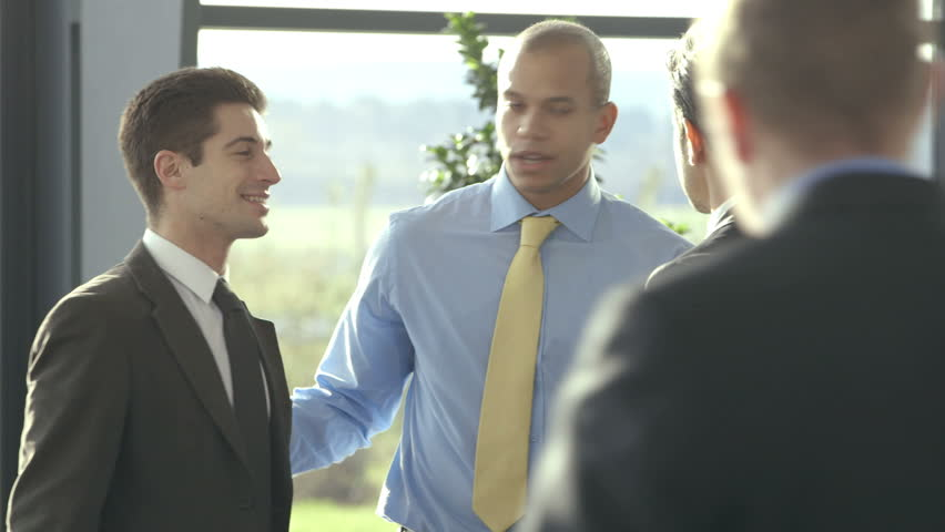Confident and attractive business team of mixed ethnicity meet and shake hands in the lobby of a busy modern office building.  - HD stock footage clip