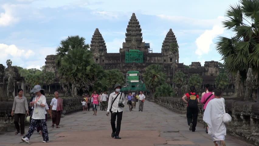 SIEM REAP, CAMBODIA - CIRCA JUNE 2011 - Tourists who visit Angkor Wat Temple walk at the main entrance.   - HD stock footage clip