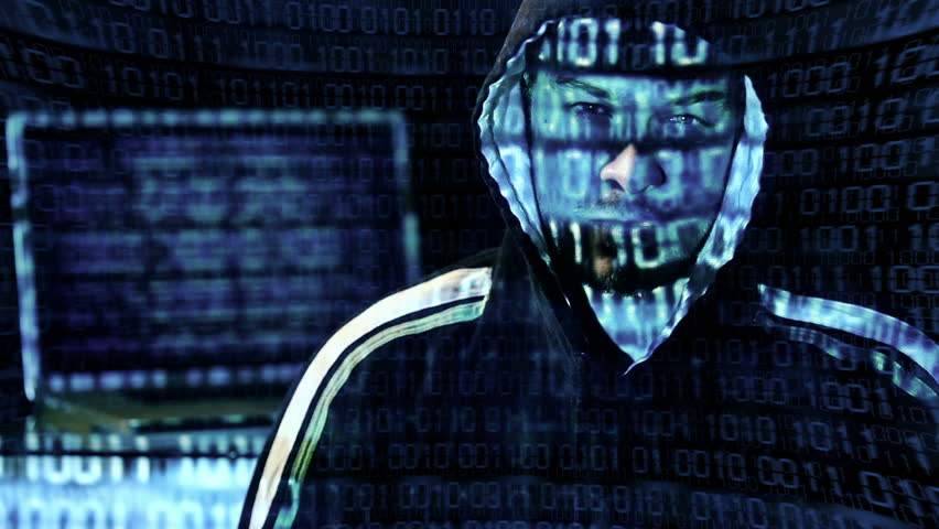 Hacker looking at the camera with laptop, binary codes projections and animation in background.