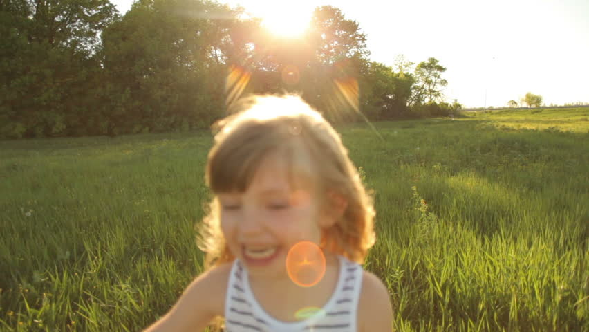 Girl running in field with smile with flare