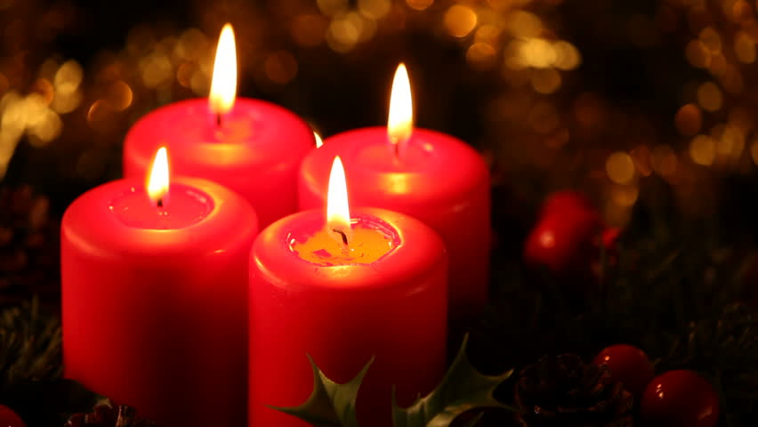 Close up of four burning candles.