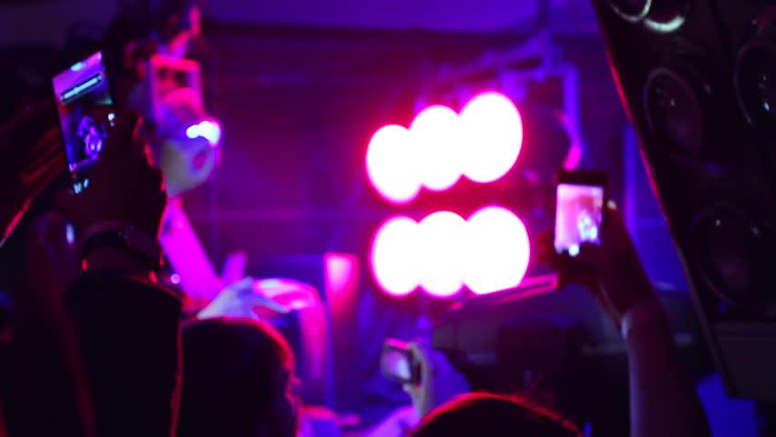 People in crowd shooting DJ using their phones in night club - HD stock video clip