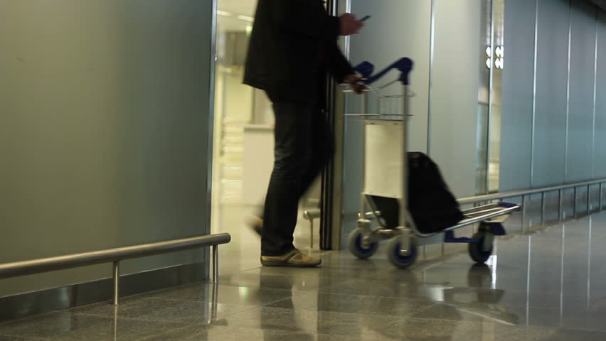 People with travel wheel bags coming out of airport arrival zone after flight - HD stock footage clip