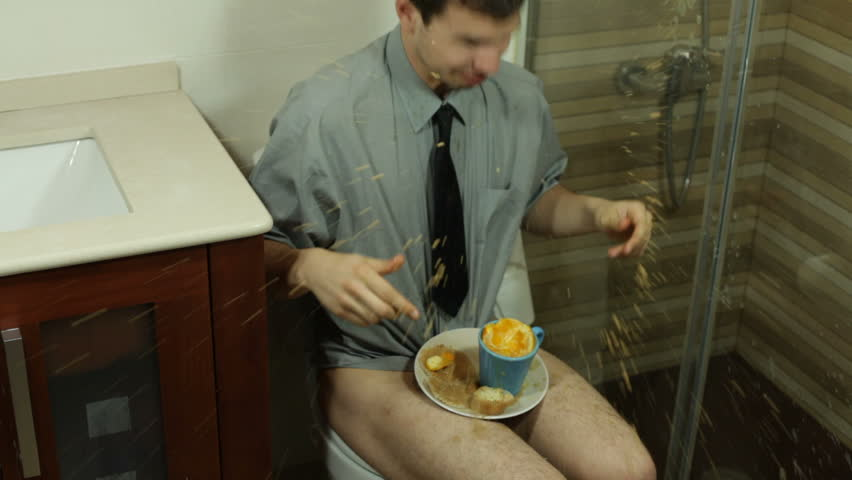 Crazy funny man eating and drinking on the toilet in bathroom