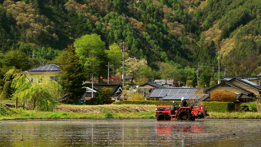Tractor plowing soil to prepare for planting rice in Nagano Prefecture, Japan.
