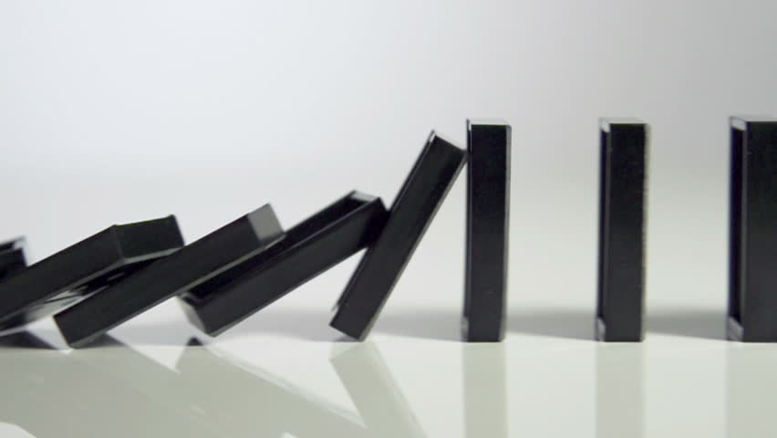 row of dominoes with one falling over on white background