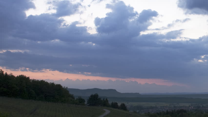 Time lapse shot of a rural sunrise with heavy clouds, going from almost night with dark blue to bright rays of sun seen through the clouds.   - HD stock video clip