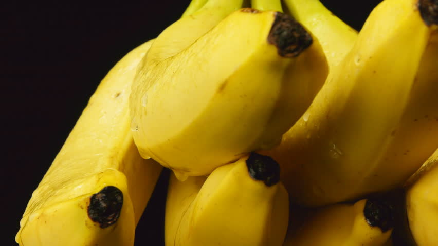 Bunch of bananas rotating on black background - HD stock footage clip