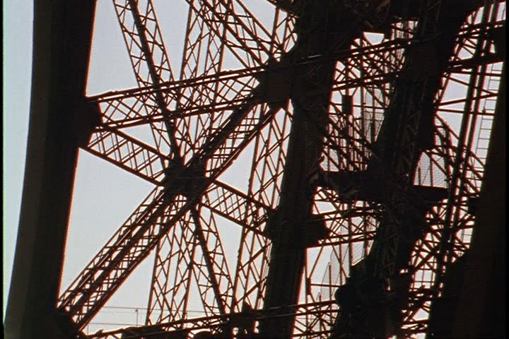 Exterior shots of the Eiffel Tower; Low angle MS of iron girders in silhouette, camera tilts up to lattice work of arch. Late day gray sky in background. - SD stock footage clip