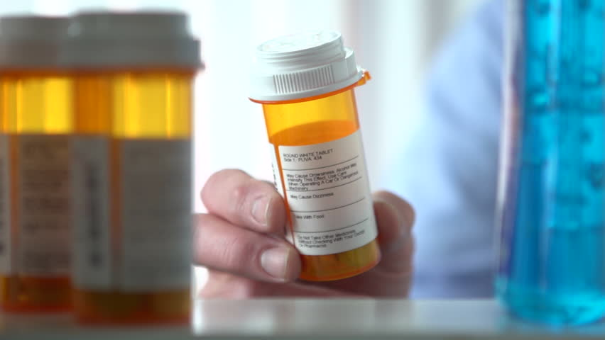 Man opens medicine cabinet, then grabs prescription medicine