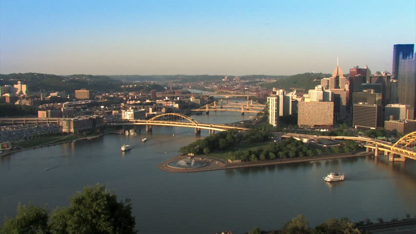 The Pittsburgh skyline, as seen from Mt. Washington.  Riverboats from The Gateway Clipper are traveling the rivers.  The corporate logos on the buildings have been removed for general use.  - HD stock footage clip
