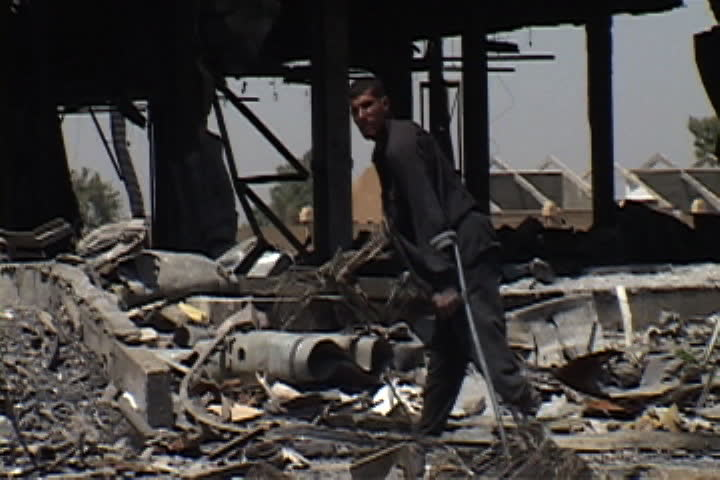 BAGHDAD, IRAQ - JULY 26, 2003: Man missing one foot walks on crutches through pile of building rubble and metal debris.