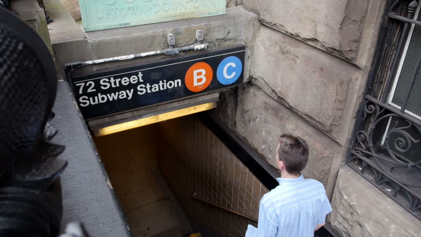 A man enters an underground subway station in New York City. - HD stock footage clip