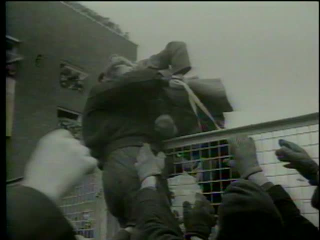 People carry fainted girl over a fence out from the Beatles fans, Heathrow Airport, London circa 1964-MGM PICTURES, UNIVERSAL-INTERNATIONAL NEWSREEL, USA, filmed in 1964
