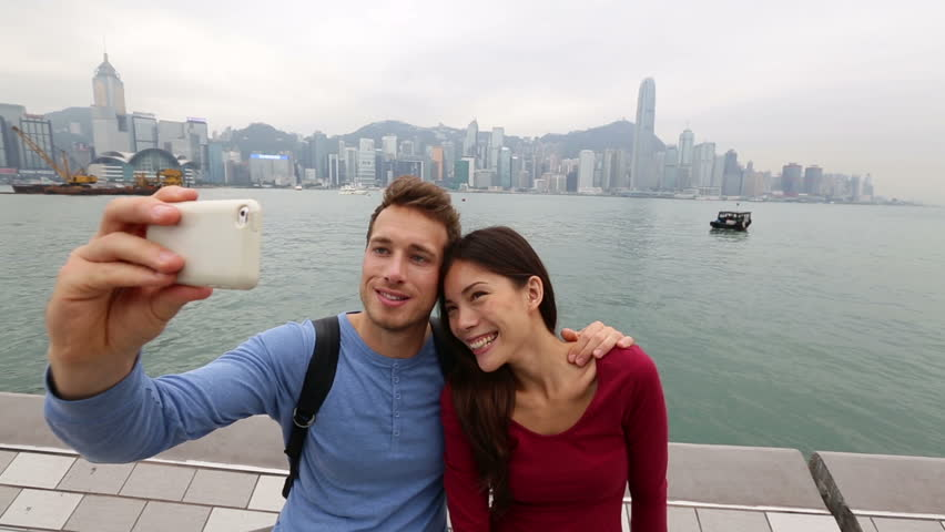 Tourists couple taking self-portrait picture photos in Hong Kong enjoying view and sightseeing on Tsim Sha Tsui Promenade and Avenue of Stars in Victoria Harbour, Kowloon, Hong Kong. Travel concept.