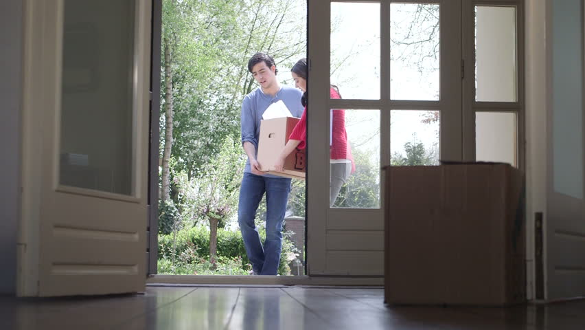 Young couple carrying cardboard box into home