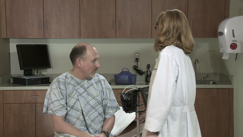 Wide view of female doctor taking the blood pressure of a mature male patient. - HD stock video clip