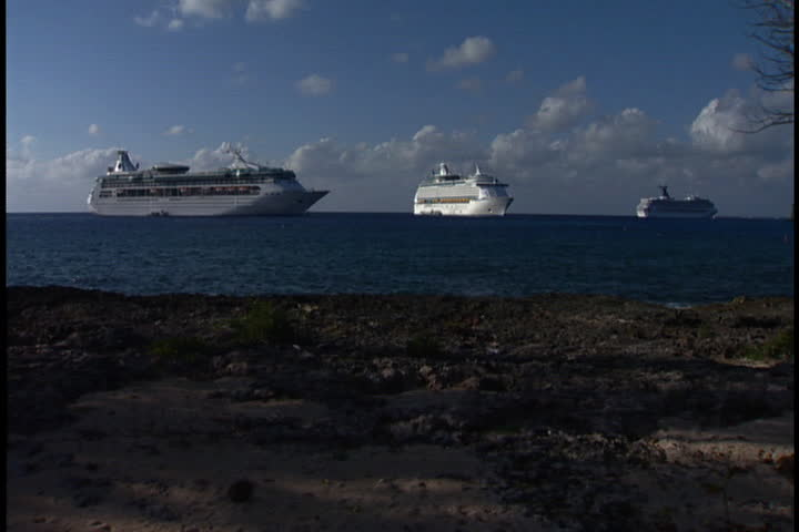 GRAND CAYMAN, CAYMAN ISLANDS - DECEMBER 11, 2003: Three cruise ships anchored off the coast of Grand Cayman Island.