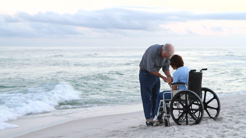 Elderly man and woman pray for healing. Woman gets out of wheelchair and the couple pray with hands lifted high.