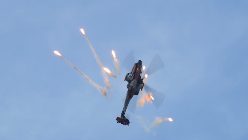 VOLKEL, NETHERLANDS - June 14 2013: An Apache AH-64 Helicopter  fires flares in a looping during an airshow at Volkel, Netherlands, June 14, 2013