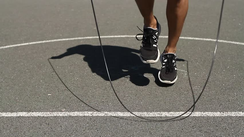 Close up shot of an athletic man skipping fancily with a jump rope - HD stock video clip