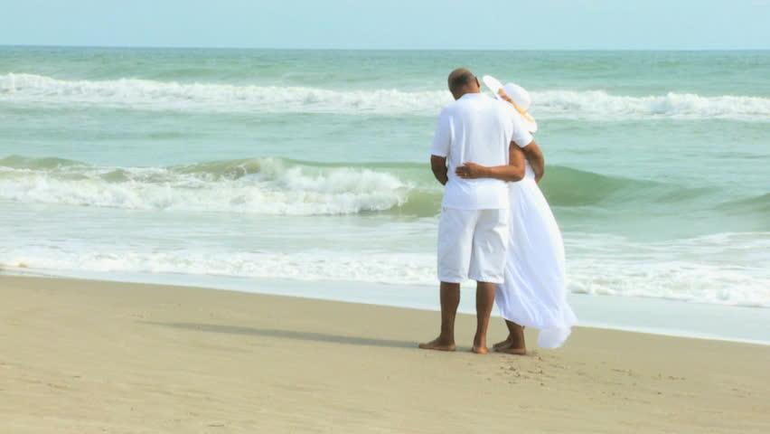 Barefoot elderly African American couple holding hands walking on beach | Shutterstock HD Video #4318379