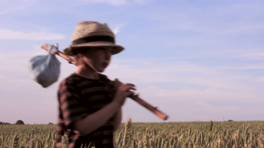 A boy wanders through a corn field with all he owns wrapped in an old bandanna on a stick. Is he a modern Sawyer or Huckleberry Finn? Perhaps he's an abandoned orphan or a child refugee far from home. - HD stock footage clip