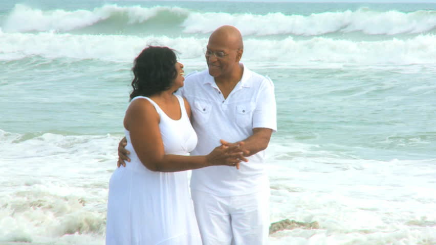 Barefoot elderly African American couple laughing dancing on beach ...