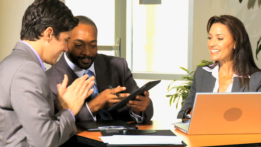 Multi ethnic group business people led by young Caucasian male receiving news of business success via tablet