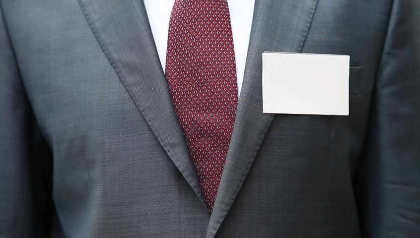 Businessman in formal suit putting blank business card on