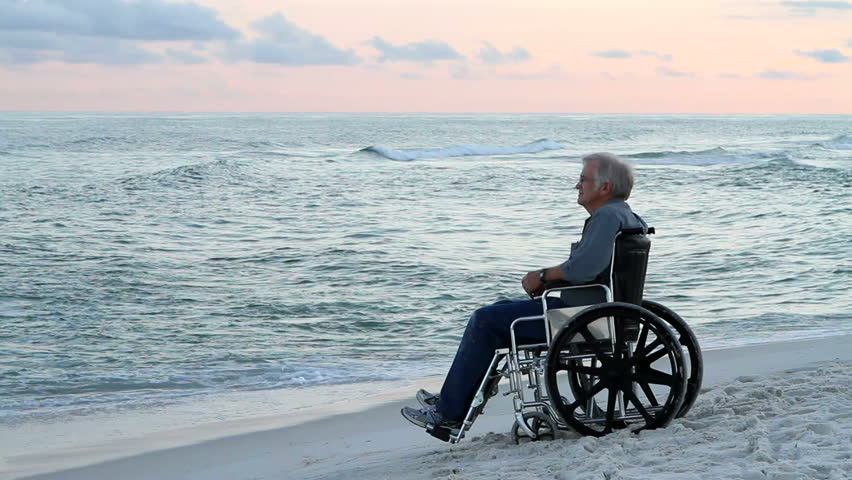 Elderly senior, physically disabled man sits in a wheelchair at the seashore watching the waves roll in and thinking. - HD stock footage clip