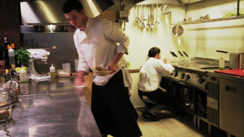 Couple of male chefs clean the steel table and in restaurant kitchen after finished the day