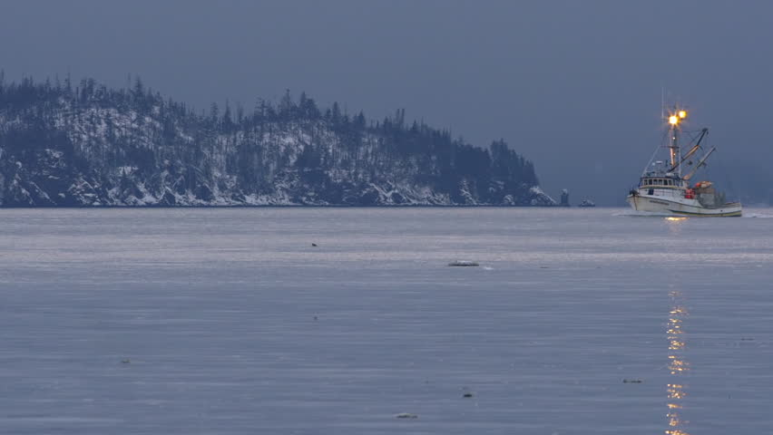 Waves of kachemak bay wash against the ice strewn beach of for Fishing in anchorage