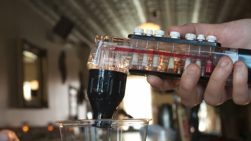 Close up on hand operating a fountain soda dispenser at a bar.  Filling glass