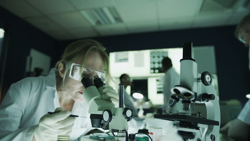 Mature male and female scientists or researchers working together in a dark laboratory, carrying out experiments with chemicals and microscope. In slow motion.   Shutterstock HD Video #4362164