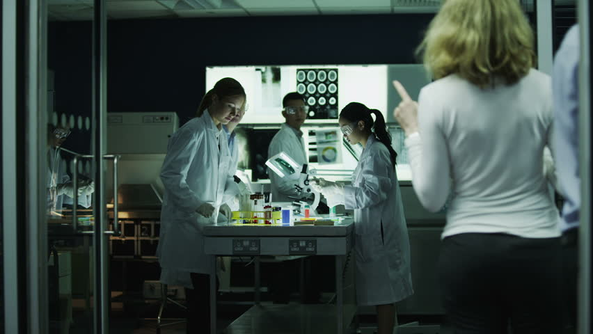 Diverse team of scientists or researchers working together in a dark laboratory, carrying out experiments and analyzing their findings.