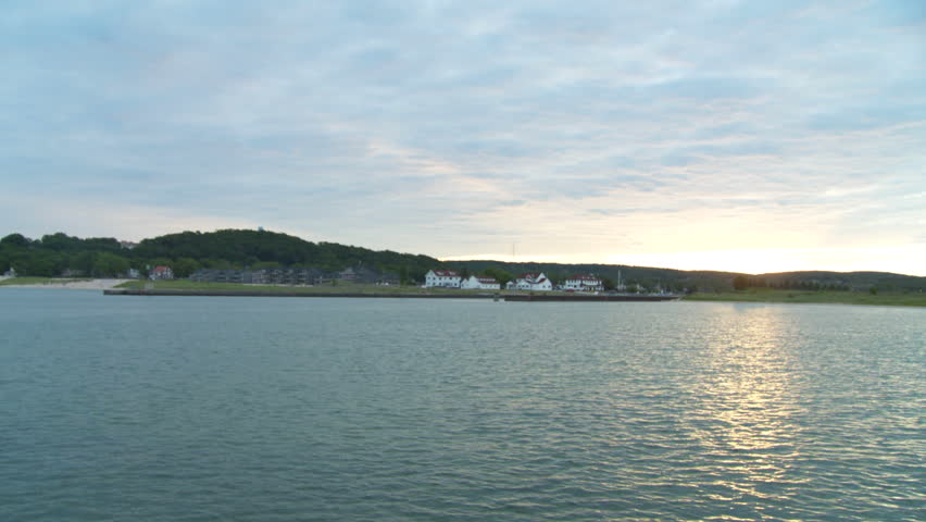 Dawn on the coast of Lake Michigan.  View of the harbor, looking towards the town of Frankfort, Michigan, with a pan around to the harbor entrance and lighthouse. - HD stock footage clip