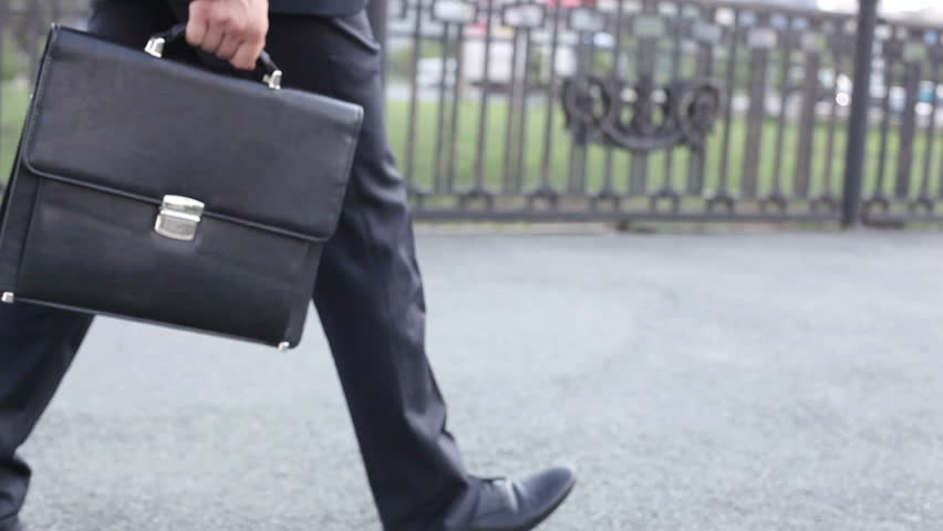 Businessman with a briefcase walking with measured steps in the urban environment