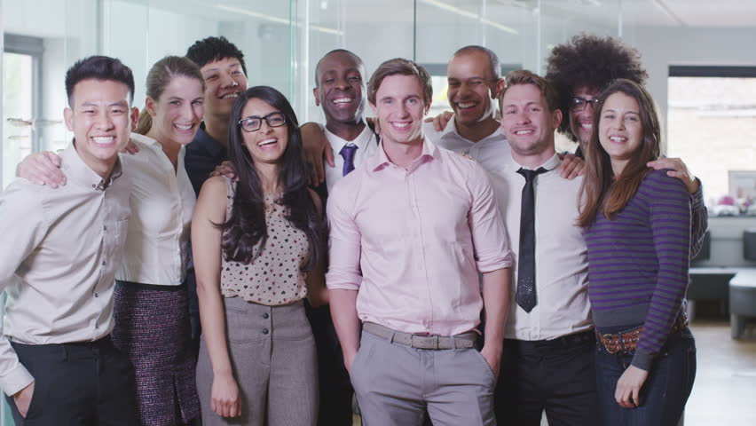 Portrait of a happy and casual young creative business team smiling and having fun together. In slow motion.