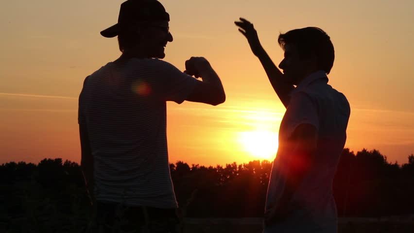 Friendship, teamwork, two male best friends enjoying dusk.