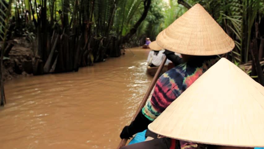 MEKONG DELTA, VIETNAM - JULY 24: woman rows a boat on a canal, Vietnam on July 24, 2013 in Mekong Delta, Vietnam
